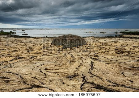 Dry crannied ground and cloudy sky on the beach. Big stone in the center. Baltic Sea coastline Estonia.