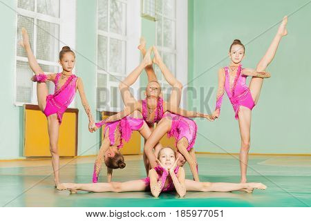 Group of six beautiful gymnast in acrobatic pose together training in the gym