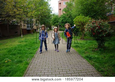 Three little friends go to school. Behind shoulders at children schoolbags. Warm spring morning. To little school students cheerfully together.