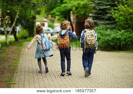 Little school students hurry on occupations. Behind shoulders at children schoolbags. Warm morning. Bright spring greens of the park.