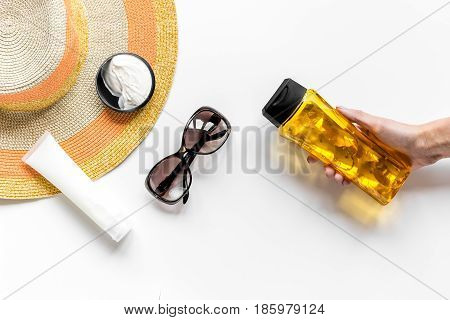Sun protection composition with glasses and body cream on white desk background top view