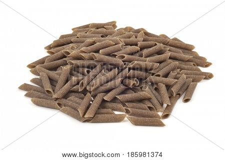 a pile of uncooked buckwheat penne rigate on a white background