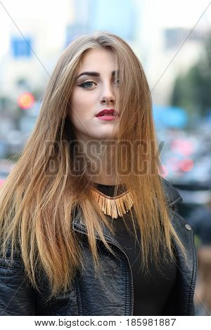 Model photo shoot in the city. Her hair moving on the wind. Fashion make-up, mouth closed, hair disbanded, leather jacket