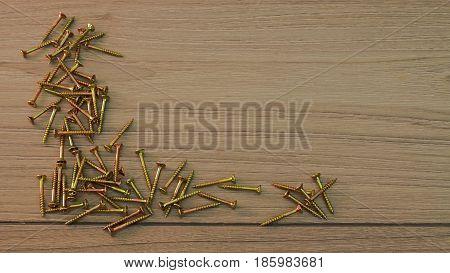 Golden steel Screws on grey wooden board