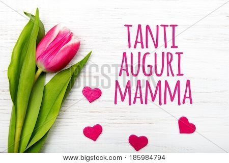 Mother's day card with Italian words: Happy mother's day. Tulip flower small hearts on white wooden background copy space