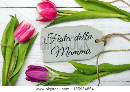 Mother's day card with Italian words: Happy mother's day. Tulip bouquet on white wooden background copy space