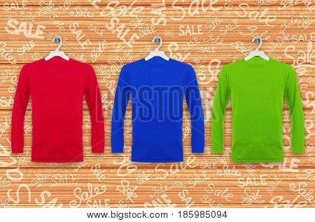 Colored T-shirts with long sleeves hanging on a wooden wall with inscriptions Sale