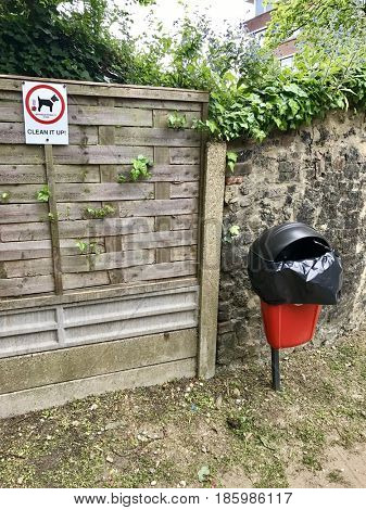 LONDON - MAY 11, 2017: A dog poo bin and fouling penalty sign beside a path in Hampstead, North London, UK.