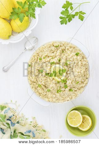 a bowl of lemon and herb Quinoa, placed on a white wooden table to ad copy space, light and airy background with green yellow and white colors.