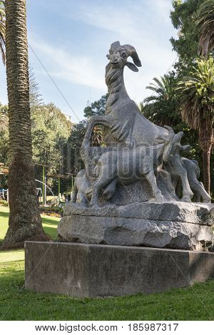 Auckland New Zealand - March 5 2017: Five Goat statue of gray Chinese granite set in green Myers Park under blue sky. Gift from Guangzhou city to celebrate Chinese immigration.