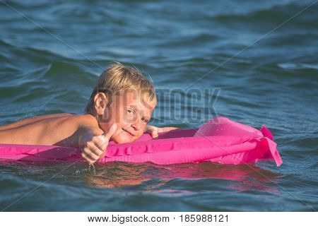 Little kid swimming in the sea on inflatable mattress and shows ok. Smiling boy playing on a water with air mattress.