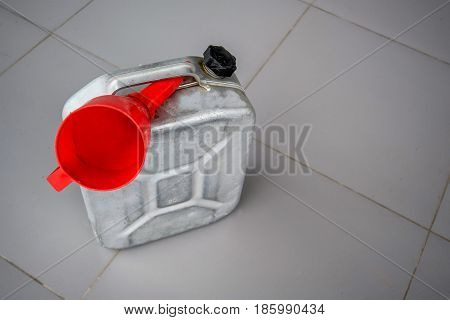 Petrol metal can with red fueling funnel