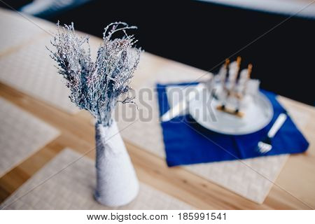 Dry flowers painted in white are in a vase on a wooden table, the breadboard model of a wooden ship is a model of a sailboat. Concept detail of the interior of the restaurant and cafe.