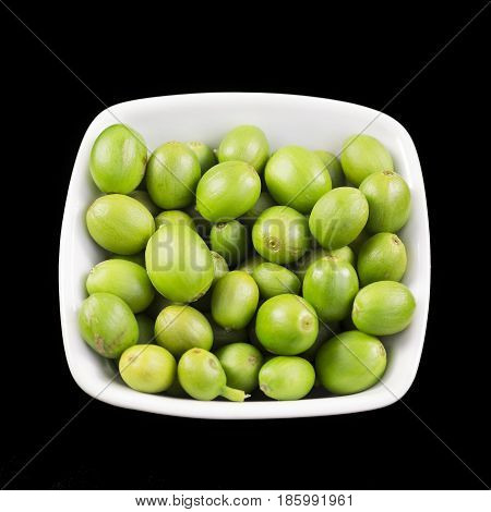 Green and unripe coffee beans in a small dish isolated on a black background