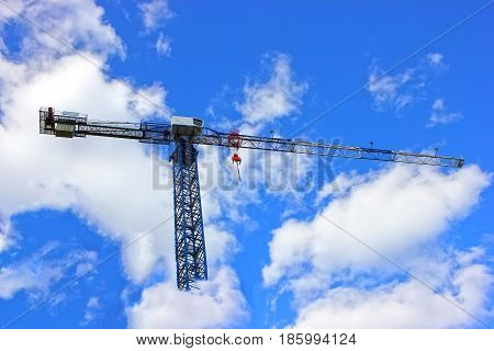 Construction crane at work site, against the blue sky, construction. Lift of a heavy cargo