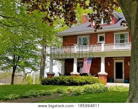old-fashioned brick house with American flag on porch