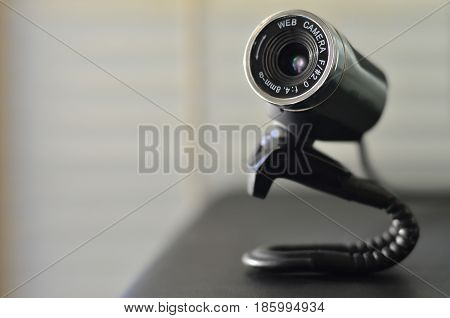 Macro photography of a wired web camera for stationary computers and laptops. A web camera image of a cylindrical shape lying on the computer surface. Focus on the camera lens