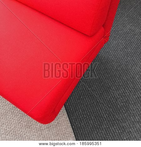 Vibrant soft red chair on gray carpet. Contemporary style furniture.