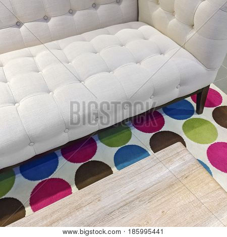 Elegant white sofa on a bright rug with colorful circles.