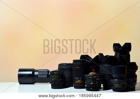 Many Different Professional Lenses For Slr Camera Lies On A Colorless Desk