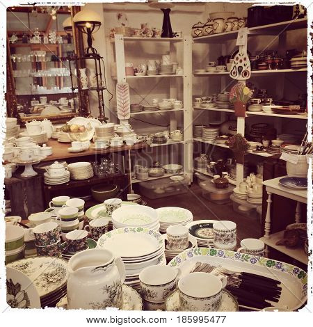Interior of a shop with vintage dishware. Sepia toned.