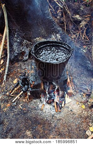 A bucket of black tar boils on the fire for use in repair and waterproofing