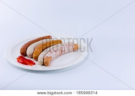 Five Different Raw German Sausage Wurst With Sliced Red Bell Pepper On A White Dish Isolated On Whit