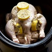 Raw chicken with lemon and herbs cooking in a slow cooker. poster