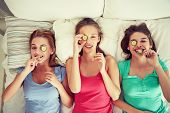 people, beauty, natural cosmetics and pajama party concept - happy friends or teenage girls with cucumber mask having fun and lying in bed at home poster