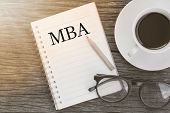 Concept MBA message on notebook with glasses pencil and coffee cup on wooden table. poster