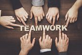 Teamwork concept. Different hands of men and women connect letters into word teamwork. Teamwork concept on the brown table. Each has its own role in team. Word teamwork out of wooden letters. poster