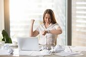 Happy businesswoman at the desk with crumpled papers looking on wristwatches and rejoices work successfully completed in time. Joyful office worker excited because of end a hard day. Cope to deadline poster
