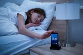 Close-up Of A Sleepy Girl Snoozing Alarm On Smartphone poster