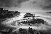 Seascape at low tide with moody clouds and pending storms and swirling ocean currents around the exposed rocks. poster