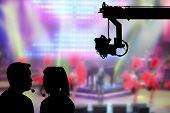 Silhouette image of the female director and cameraman or photographer talking or consulting to working with hanging cemara on crane on blurry concert on stage background in television studio poster