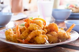 Fried prawn balls on a wooden table backgrounded with bowls and cups