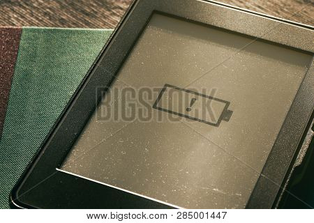 Low Battery Icon On E-book E-reader Screen With Warm Sunlight