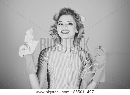 Retro woman cleaner on pink background. Housekeeper in uniform with clean spray, duster. Cleaning, retro style, purity. Cleanup, cleaning services, wife, gender. Pinup woman hold soup bottle, duster. poster