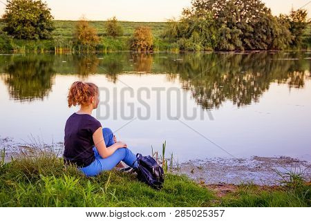 A Young Girl Sits On The Riverbank And Contemplates The Beauty Of The Surrounding Nature