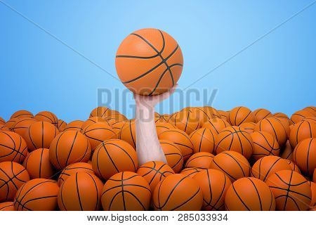 Hand Appearing Out Of Heap Of Orange Basketball Balls Holding One On Blue Background