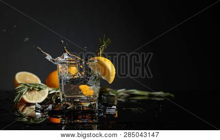 Cocktail Gin-tonic With Lemon Slices And Twigs Of Rosemary. Piece Of Ice Falls Into The Glass. Copy