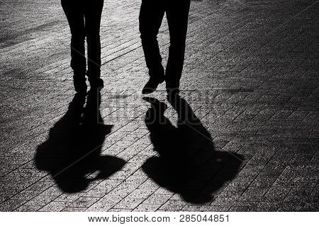 Couple Walking Down The Street, Silhouettes And Shadows Of Two People On Pedestrian Sidewalk. Male A