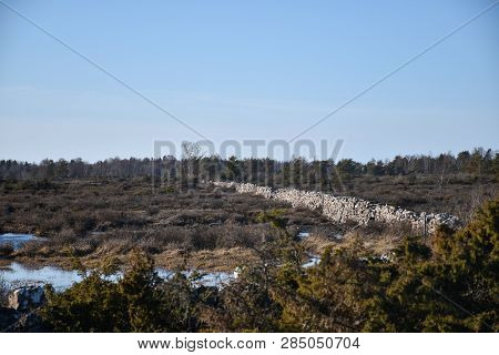 Old Dry Stone Wall In A Plain Landscape At The Swedish Island Oland