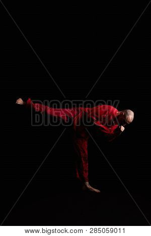 Male In Red Costume Practicing Qigong In The Dark