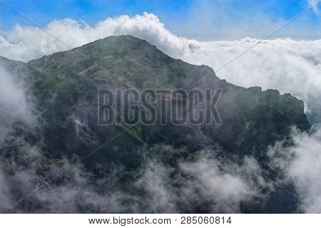Mountain Peak In Dense Clouds Against Blue Sky. View From Pico Do Arieiro On Portuguese Island Of Ma