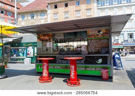 GRAZ, AUSTRIA - JULY 2018 : Austrian fast food shop, sausage stand in Graz, Austria on July 20, 2018. It's called Schnellimbiss in German language