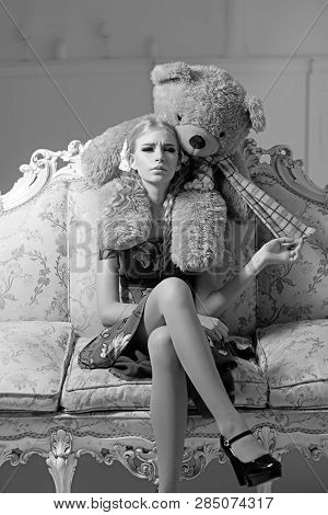 Young spoiled aristocrat sitting on vintage sofa. Blond lady playing with her huge teddy bear. poster