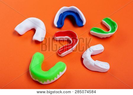 Lots Of Boxing Protective Mouthguards On Orange Background, Concept