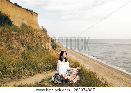 Young Beautiful Woman Relaxing And Practicing Yoga On Beach, Sitting In Grass And Sand, Meditating A