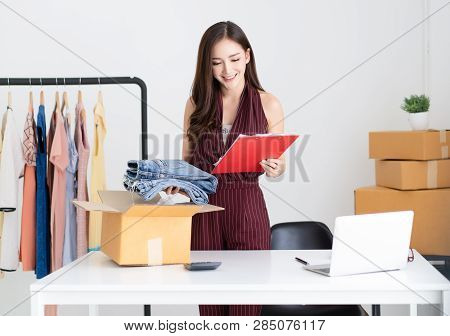 Young Asian Casual Woman Working Small Business Online Packing Jeans To Cardboard Box In Home Office
